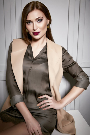 sits on a chair: Beautiful young sexy brunette woman wearing a short silk dress stylish design and fashionable jacket , beige heels shoes long thin legs, body shape sits on chair, make-up, party makeup fashion style