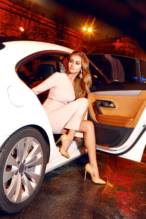 Beautiful young sexy blonde wearing evening makeup in elegant fitting dress fashionable stylish sitting in cabin of expensive car comes out of it in hand  handbag luxury rich life going party concert