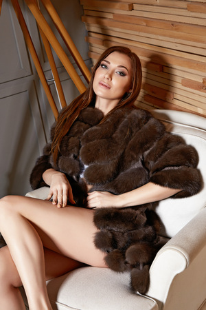 woman fur: Beautiful young sexy brunette woman wearing a short dress stylish design and fashionable fur coat, beige heels shoes long thin legs, body shape sits on chair, makeup, party fashion style winter