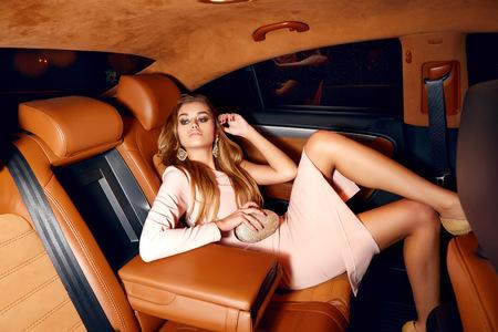 Mooie jonge sexy blonde dragen avond make-up in een elegante passende kleding modieus stijlvol zitten in de cabine van de dure auto eruit komt in de hand handtas luxe rijk leven gaan party concert