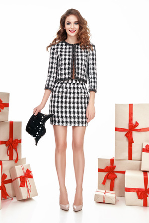 dress shoes: Beautiful young sexy woman thin slim figure evening makeup fashionable stylish dress, clothing collection, brunette, gifts boxes red silk bows holiday party birthday New Year Christmas Valentines Day Stock Photo