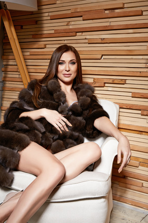 Beautiful young sexy brunette woman wearing a short dress stylish design and fashionable fur coat, beige heels shoes long thin legs, body shape sits on chair, makeup, party fashion style winter