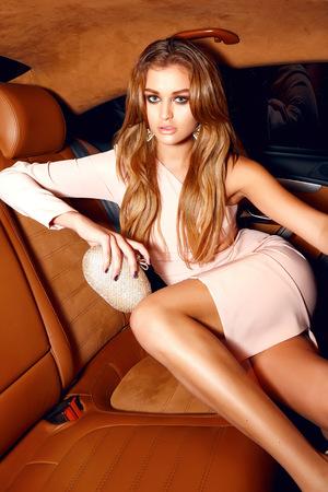 비싼 차의 오두막에서 우아한 맞춤 드레스 유행 세련된 앉아 아름 다운 젊은 섹시한 금발 입고 저녁 메이크업은 파티 콘서트를가는 손 핸드백 명품 풍