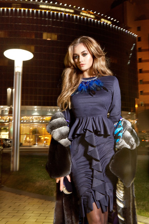 rich life: Beautiful young sexy blonde wearing evening makeup in elegant fitting dress fashionable stylish expensive fur coat walk night street lights evening hand  handbag luxury rich life going party concert