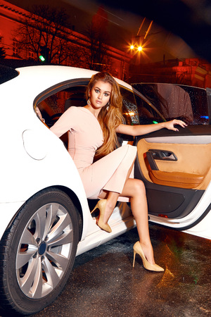 rich life: Beautiful young sexy blonde wearing evening makeup in elegant fitting dress fashionable stylish sitting in cabin of expensive car comes out of it in hand  handbag luxury rich life going party concert