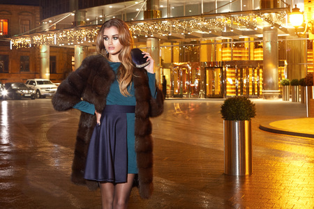 celebrities: Beautiful young sexy blonde wearing evening makeup in elegant fitting dress fashionable stylish expensive fur coat walk night street lights evening hand  handbag luxury rich life going party concert