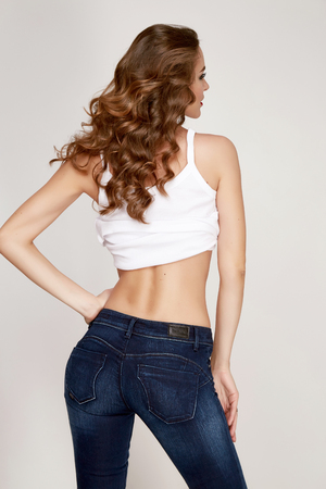 Beautiful sexy young woman dressed in a black tight-fitting skinny denim jeans figure stands with his back to, brunette hair, make-up hair, red lipstick, clothing Фото со стока
