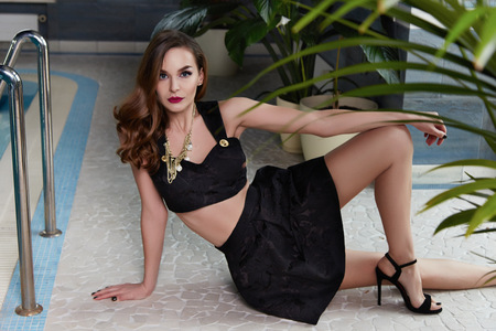 Beautiful sexy brunette in a stylish fashion designer suit skirt and top in sandals high heels color makeup and dark curly hair sitting floor tiles around pool palm summer vacation hotel woman dress