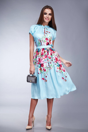Beautiful young brunette girl woman lady dressed in a pale blue silk handbag and belt Accesories long dark hair, make-up and cosmetics, catalog of everyday and festive dress, sexy style and fashion