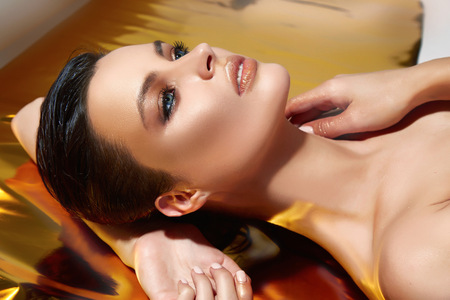 collo: Bello ritratto sexy bruna ragazza sdraiata sul fondo oro lucente, notte di festa trucco, ciglia lunghe lussureggianti, paffuto labbra socchiuse, cosmetici, cura del corpo, spalle collo pelle morbida, tan bronzo