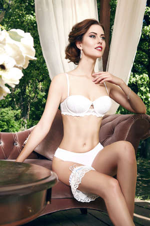 clothing model: Woman in a white lace silk lingerie sits in a chair by the window next to orchid flower gentle look, stylish trendy underwear set soft skin perfect body shape bride before the wedding jewelry makeup Stock Photo