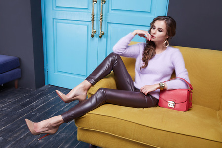 아름 다운 섹시 한 갈색 머리 여자 세련된 유행 꽉 바지 에코 가죽 캐시미어 스웨터, 의류 카탈로그, 빨간 가방, 방 인테리어, 도어를 입고 소파에 앉아.