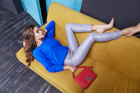Stylish fashionable beautiful girl lying on the sofa well dressed in leather trousers, a bright blue wool cardigan, make-up, high heels shoes room.