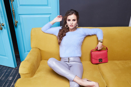handbag model: Woman sitting on a yellow couch behind the door style fashion trend, a beautiful young lady, dressed in slacks and sweater, stylish handbag accessories, makeup hairstyle party. Stock Photo