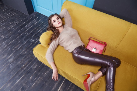 Woman wear cashmere sweater and leather trousers seat on the yellow sofa blue door furniture interior clothes fashion collection bag.