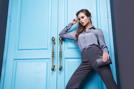 Beautiful sexy girl dressed style of fashion clothing new catalog of the collection, modern, stylish pants, fancy silk shirt accessory shoes with high heels, interior room with blue door entrance exit.