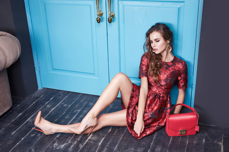 Beautiful young sexy woman in smart evening dress red silk dress new stylish fashion collection autumn winter season, long brown hair, shoes, interior blue door in the bedroom room. Фото со стока