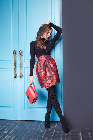 fashion magazine: Stylish fashionable outfit slim beautiful girl figure diet, catalog collection of clothing, attractive, sexy woman wearing red skirt classic fitting black sweater, leather small handbag room blue door.