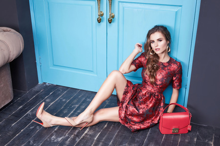 Beautiful fashionable stylish woman dressed in sexy short dress made natural fabrics bordeaux collection long hair makeup, fashion, style, interior gray room blue door holding a leather bag accessory