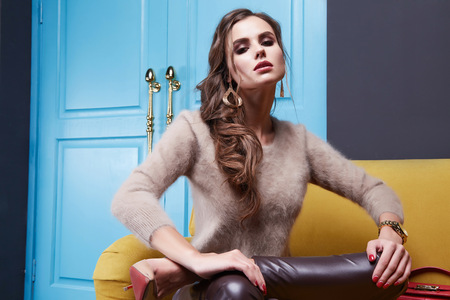 blue leather sofa: Woman wear cashmere sweater and leather trousers seat on the yellow sofa blue door furniture interior clothes fashion collection bag.