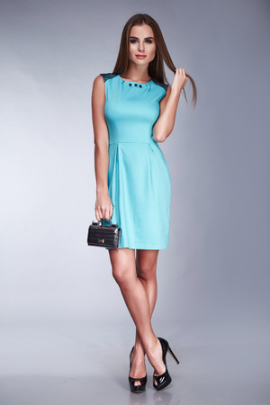 Beautiful young sexy woman lady stylish elegant fashionable dress, makeup and hair style for the evening business meeting walk date designer dress with accessories and ornaments high heels hold bag