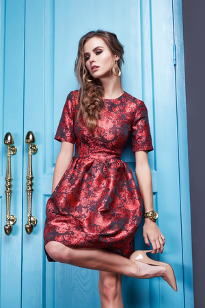Beautiful young sexy woman in smart evening dress red silk dress new stylish fashion collection autumn winter season, long brown hair, shoes, interior blue door in the bedroom room. Stock Photo