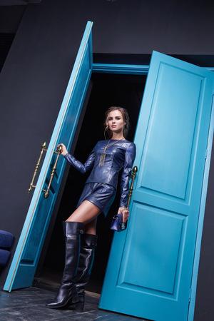 セクシーな美しい女性は、青いドア内部のフットウェア コレクション メイクアップ化粧品アクセサリー バッグ水色の革衣装ファッション スタイル