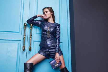 Sexy mooie vrouw dragen blauw lederen kostuum mode-stijl jurk accessoiretas cosmetische make-up. Stockfoto