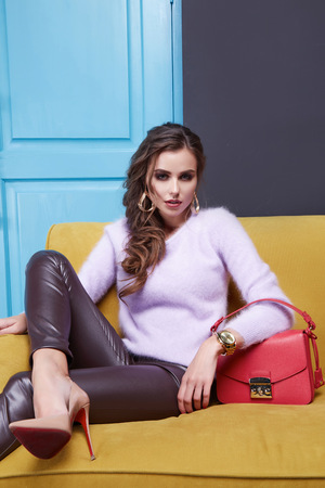 leather sofa: Beautiful sexy brunette woman sitting on a couch, wearing a stylish fashionable tight pants eco leather cashmere sweater, clothing catalog, red bag, room interior, door