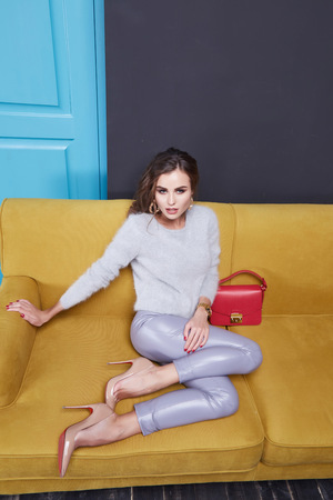 blue leather sofa: Woman wear cashmere sweater and leather trousers seat on the yellow sofa blue door furniture interior clothes fashion collection bag Stock Photo