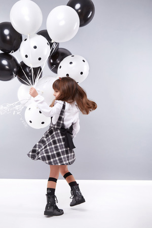 Little girls girlfriend in a beautiful stylish fashion clothes new collection of dress suit, are holding balloons, birthday celebration, congratulations, fun party for kids, dance smile