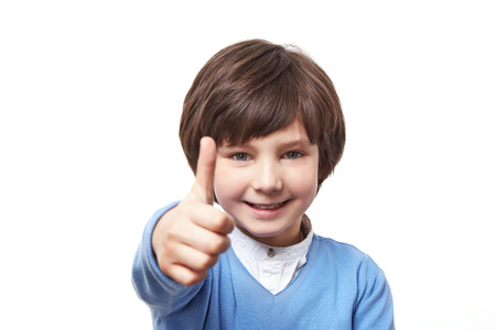 manful: Cute little boy with dark hair reaches out forward the emotion perfectly satisfied approval, dressed in a blue sweater on a white background Stock Photo