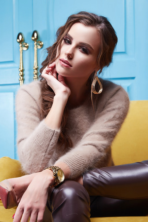blue leather sofa: Beauty sexy woman wear cashmere sweater and leather trousers seat on the yellow sofa blue door furniture interior clothes fashion collection  casual trend gold jewelry Stock Photo