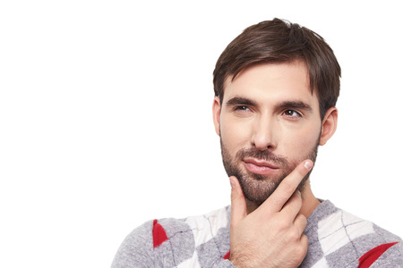 manful: Handsome attractive brunette man guy with a beard stubble in a checkered sweater leaned his hand to face thought reflects remembers dreams on a white background