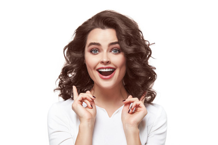 spunky: Beautiful sexy attractive brunette woman with makeup smile teeth in a white blouse raised her hands up something invented, guessed remembered surprised to realize, drew attention Stock Photo