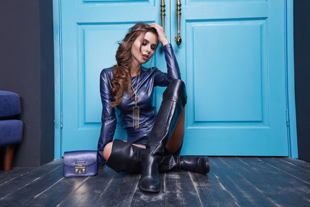 designer bag: Sexy beautiful woman wear blue leather costume fashion style clothes accessory bag cosmetic make up blue door interior wear collection.