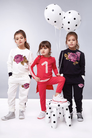 best party: Small baby girls sisters in a beautiful style fashion clothes collection of dress suit silk skirt, holding balloons, birthday celebration, congratulations, fun party for kids, dance smile jump