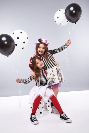 Small baby girls sisters in a beautiful style fashion clothes collection of dress suit silk skirt, holding balloons, birthday celebration, congratulations, fun party for kids, dance smile jump