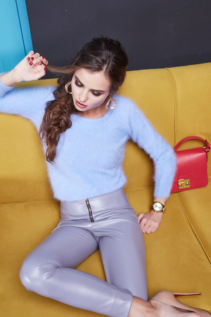 blue leather sofa: Beautiful woman lady wear cashmere sweater and leather trousers seat on the yellow sofa blue door furniture interior clothes fashion style sexy collection brand bag store sale Stock Photo