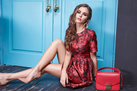 sexy shoes: Beautiful young sexy woman lady in elegant evening dress red silk dress new stylish fashion collection long brown hair, shoes, interior blue door in bedroom room meeting, party style brand lather bag Stock Photo