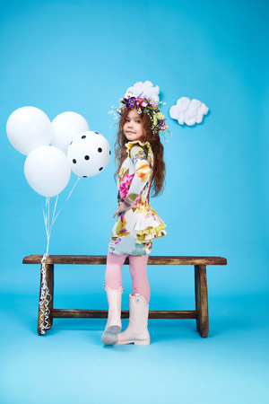 Small little beautiful pretty cute girl dark hair hat with flowers wear fashion style trend clothing dress skirt blouse shoe smile play with bench and balloons dance jump children kid happy daughter Stock Photo