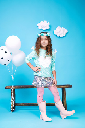 Small little beautiful pretty cute girl dark hair hat with flowers wear fashion style trend clothing dress skirt blouse shoe smile play with bench and balloons dance jump children kid happy daughter Standard-Bild