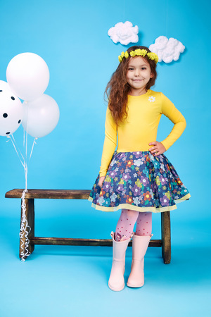 Small little beautiful pretty cute girl dark hair hat with flowers wear fashion style trend clothing dress skirt blouse shoe smile play with bench and balloons dance jump children kid happy daughter Archivio Fotografico