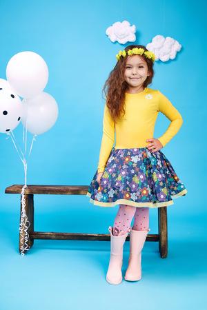Kleine mooie meisje mooie dame donker haar hoed met bloemen dragen stijl trend kleding rok blouse schoen glimlach mode te spelen met bank en ballonnen dans springen kinderen kid blij dochter