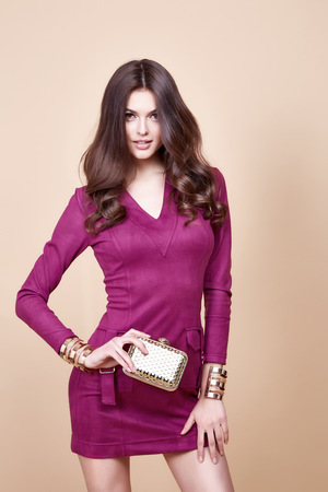 Glamour beautiful sexy brunette women, looks like a model, wearing evening make up in short red dress with small yellow bag in hands in fashion pose with amazing figure, perfect shape girl hairdo. Stockfoto