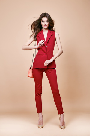 Beautiful brunette woman wear red silk costume jacket and pants summer collection clothes for business lady casual work office style hold small lather goods bag make a pose fashion model catalog.