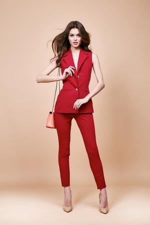 Mooie sexy brunette vrouw draagt rode zijde kostuum jas en broek zomer collectie kleding voor het bedrijfsleven dame tijdelijk werk kantoor stijl houden kleine schuim producten zak maak een pose mannequin catalogus.