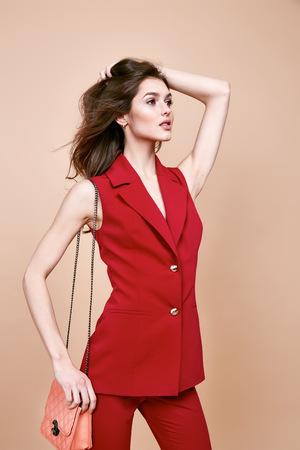 Beautiful sexy brunette woman wear red silk costume jacket and pants summer collection clothes for business lady casual work office style hold small lather goods bag make a pose fashion model catalog. 版權商用圖片 - 54633048