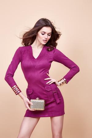 poses de modelos: Glamour bellas mujeres sexy morena, se parece a un modelo, uso de la noche a recompensar en el corto vestido rojo con el pequeño bolso de color amarillo en las manos en actitud de la manera con la figura increíble, perfecto peinado niña de forma.