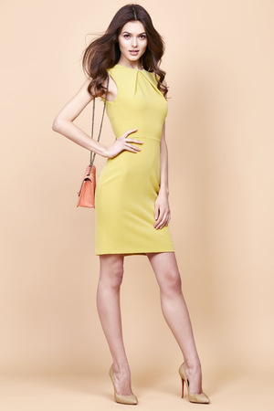 cotton dress: Glamour fashion woman long brunette curly hair natural evening makeup wear sexy short stylish yellow cotton dress from new catalog spring summer collection accessory handbag jewelry body shape care.